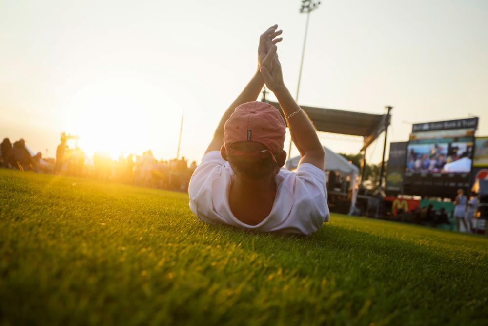 Man laying on grass enjoying music at Fargo Blues Festival