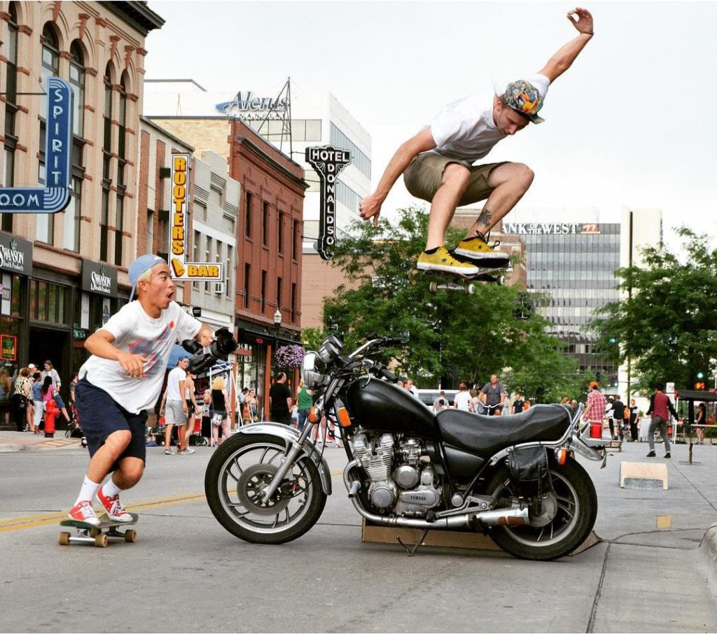 skateboarder jumps over motorcycle at streets alive in downtown Fargo