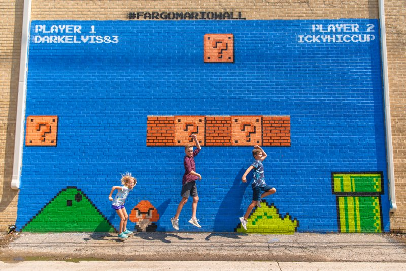 kids jumping in front of Fargo Mario Wall mural