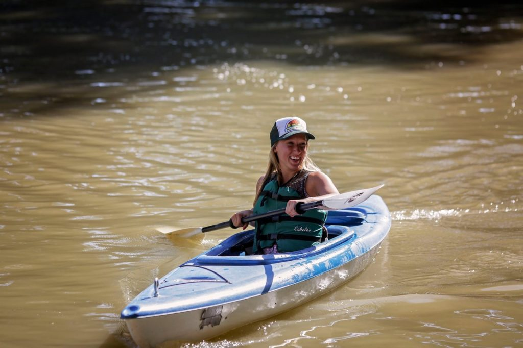 Person smiling while kayaking on the Red River in a rented kayak in Fargo Moorhead